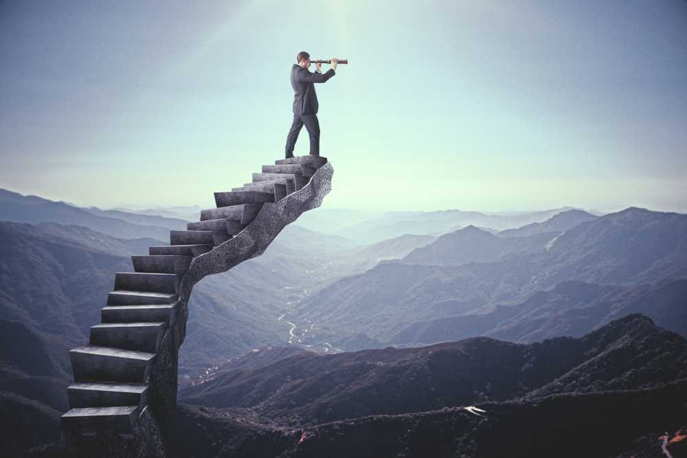 Businessman looking into the distance on abstract stairs
