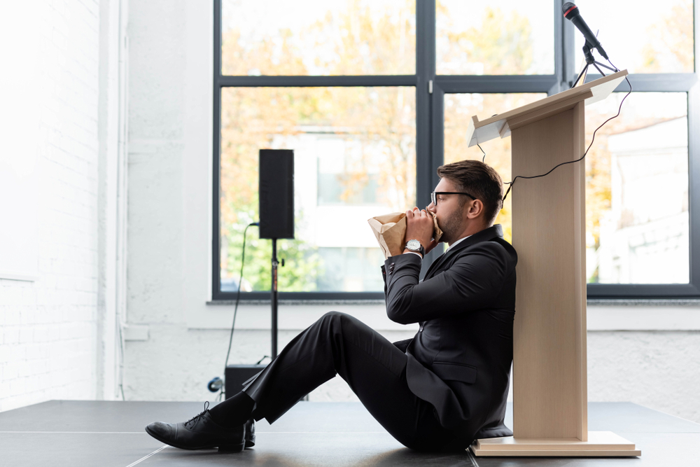 ide view of scared businessman in suit breathing in paper bag during conference