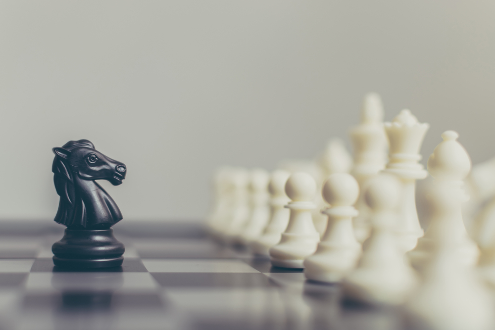 Business leader and confrontation solve problems concept, Chess board game, black knight confronting white pieces